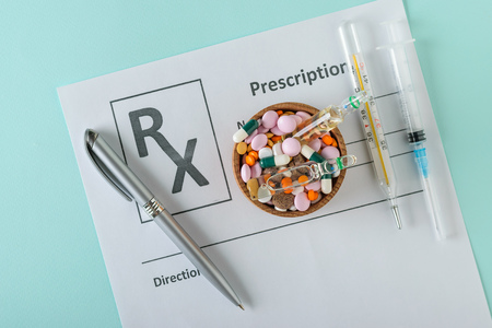 Syringe, thermometer, pen and bowl with pills on a sheet with a doctor's prescription. The view from the top. The concept of treatment and prevention of diseases. Flat lay. Stock Photo - 116863884