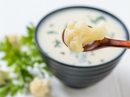 An inflorescence of cauliflower in a brown wooden spoon over a bowl of cream soup. Keto diet dish.