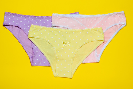 Three womens cotton panties on a yellow background. Fashionable concept. Beautiful lingerie. Fashionable concept. Beautiful lingerie.