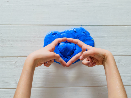 Child hands shows heart of over blue slime. Toy antistress. Toy for the development of hand motor skills.