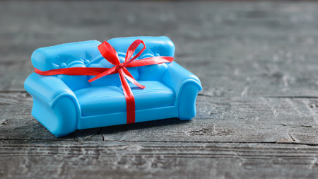 Blue sofa tied with a red gift ribbon on the black wooden floor. Unusual gift. Minimalist.