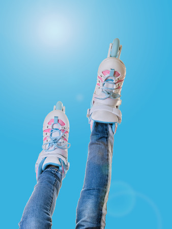 Girls feet in roller skates on blue background with glare. The concept of sports lifestyle.