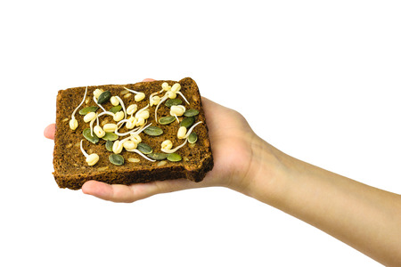 A piece of bread with sprouted beans and pumpkin seeds in hand isolated on white. Dietary vegetarian food from sprouted grains.