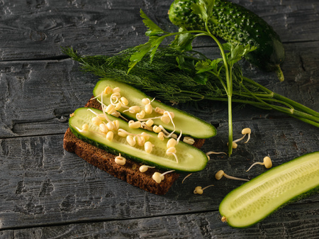 A piece of bread with sprouted beans and pumpkin seeds with cucumber on a black wooden table. Dietary vegetarian food from sprouted grains.
