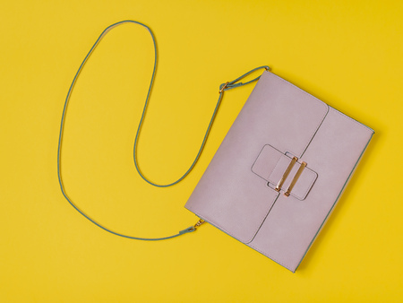 Light leather women's bag on yellow background. Modern women's leather accessory. The view from the top.