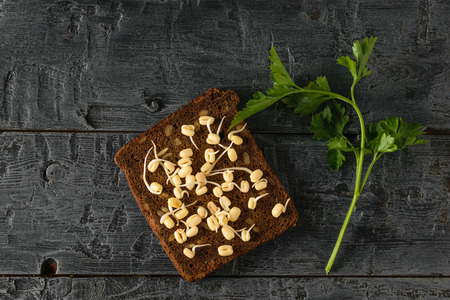A piece of dark bread with sprouted mung beans and a sprig of parsley on a black wooden table. Dietary vegetarian food from sprouted grains. The view from the top.
