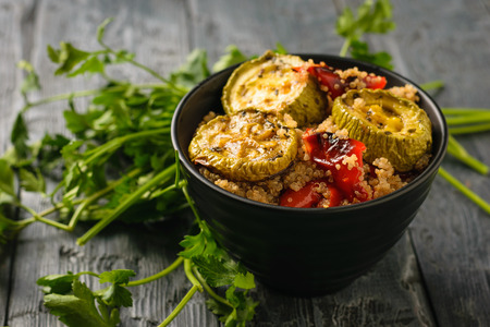 Parsley leaves and baked vegetables in a bowl on a wooden table. Vegetarian dish. Natural healthy food.