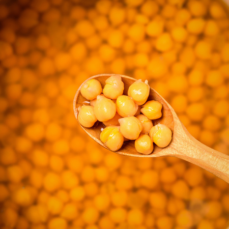 Wooden spoon with boiled chickpeas on the background of a bowl of beans. Vegetarian cuisine from legumes. The view from the top.