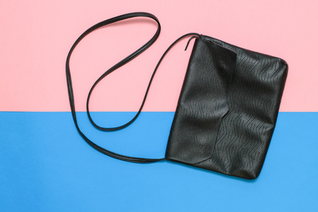 Black womens bag with strap on pink and blue background. Modern womens leather accessory. The view from the top. Reklamní fotografie