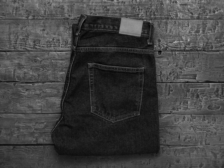 Black and white image of stylish mens jeans on a wooden table. Classic denim clothing. Flat lay. The view from the top.