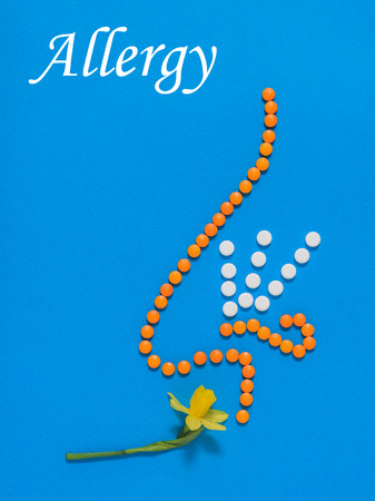 Nose of pills and yellow flower on blue background. Allergic to spring flowers. The concept of treatment of diseases of the nose and allergies. Flat lay. The view form the top.