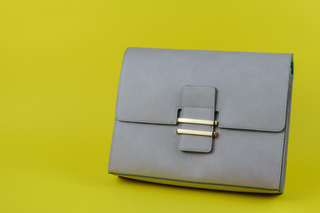 Light gray women's bag on a bright yellow background. Modern women's leather accessory. 스톡 콘텐츠