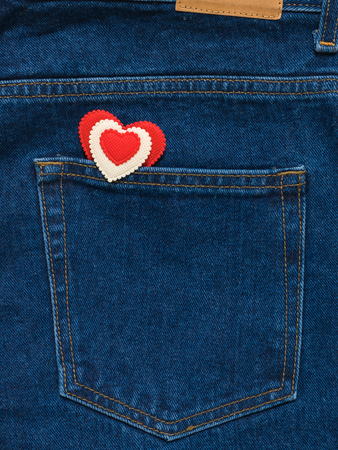 Red and white heart in the pocket of bright blue jeans. Romantic style in fashionable clothes.