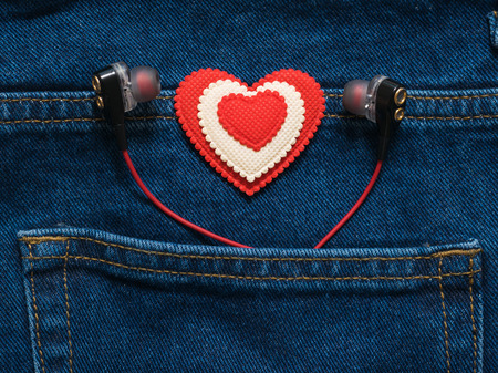 Red and white heart with headphones sticking out of the pocket of jeans. Romantic style in fashionable clothes.