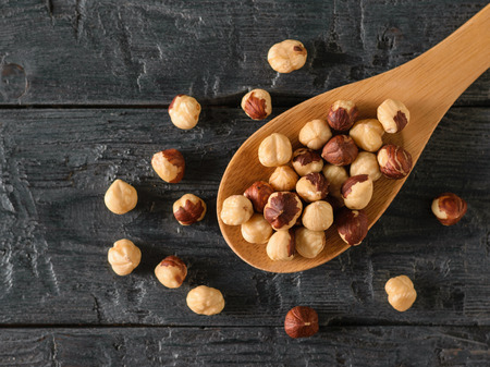 Wooden spoon with roasted hazelnuts on a rustic table. Prepared with the harvest of hazelnuts. The view from the top.