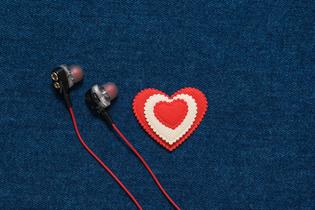 Red headphones and a red and white heart on a denim background. Romantic style in fashionable clothes.