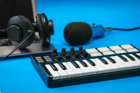 Music mixer, laptop and blue microphone with wires on blue background. Equipment for recording music tracks.
