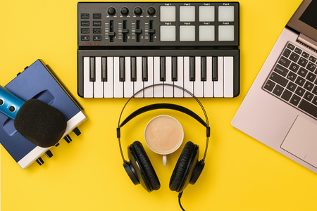 Music mixer,microphone, headphones and sound card on yellow background. The concept of workplace organization. Equipment for recording, communication and listening to music. Reklamní fotografie