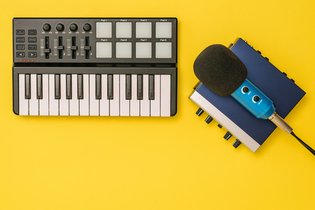 Sound card, music mixer and microphone on yellow background. The concept of workplace organization. Equipment for recording, communication and listening to music. Reklamní fotografie - 122410784