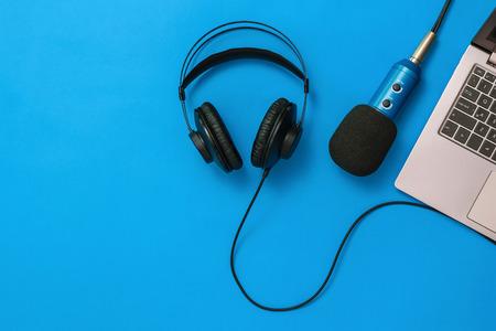 Un ordinateur portable avec un microphone et un casque connectés sur fond bleu. Le concept d'organisation du lieu de travail. Équipement pour l'enregistrement, la communication et l'écoute de la musique. Mise à plat.