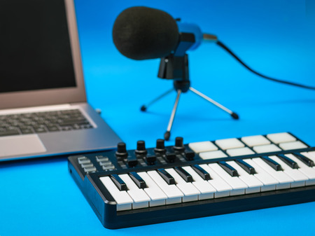 Music mixer, laptop and microphone with wires on blue background. Equipment for recording music tracks. Stock Photo