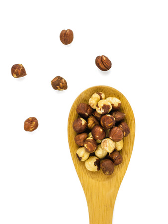 Roasted hazelnuts in a spoon isolated on white background. Prepared with the harvest of hazelnuts. The view from the top. Stock Photo