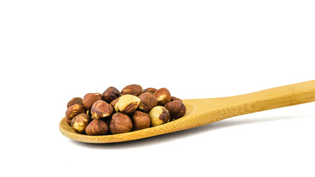 Wooden spoon with roasted hazelnuts isolated on white background. Prepared with the harvest of hazelnuts. Stock Photo