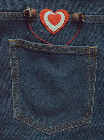 Toned image of the pocket of jeans with headphones and a red-and-white heart. Romantic style in fashionable clothes.