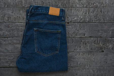 Mens blue jeans on a dark wooden table. Classic denim clothing. Flat lay. The view from the top. Banco de Imagens