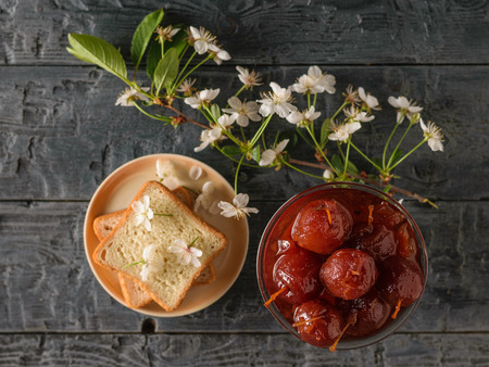 A bowl of Apple jam, bread, and a branch of flowers on a dark table. Homemade sweets according to old recipes. Flat lay.