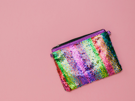 Multi-colored womens bag on a pink background. Fashion womens accessory. Flat lay. The view from the top.