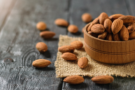 Almonds in a wooden bowl on a piece of burlap on a dark wooden table. Vegetarian food. Banco de Imagens