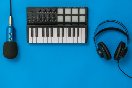 Music mixer,microphone and headphones on blue background. The concept of workplace organization. Equipment for recording, communication and listening to music. Reklamní fotografie