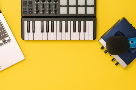 Music mixer, sound card, laptop and microphone on yellow background. The concept of workplace organization. Equipment for recording, communication and listening to music.