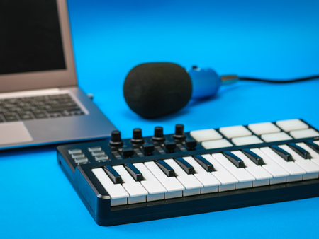 Music mixer, open laptop and microphone with wires on blue background. Equipment for recording music tracks. Banco de Imagens