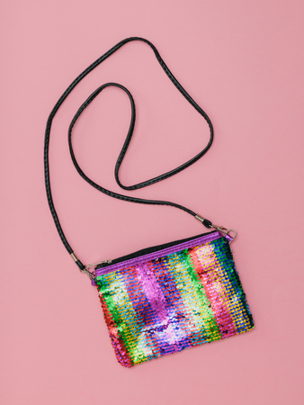 Multi-colored womens bag with strap on pink background. Fashion womens accessory. Flat lay. The view from the top.