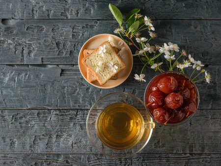 Apple jam, tea, bread and a sprig of cherry blossoms on a dark table. Homemade sweets according to old recipes. Flat lay.