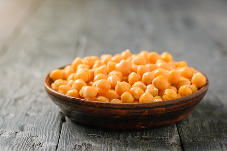Boiled chickpeas in a clay bowl on a black wooden table. Minimalism. Vegetarian cuisine from legumes.