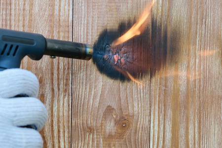 Hand in a glove with a burner performs firing of wooden panels. Treatment of the wooden surface fire. Decoration of wood texture.