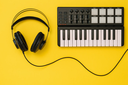 Headphones and music mixer on bright yellow background. The concept of workplace organization. Equipment for recording, communication and listening to music. Banco de Imagens