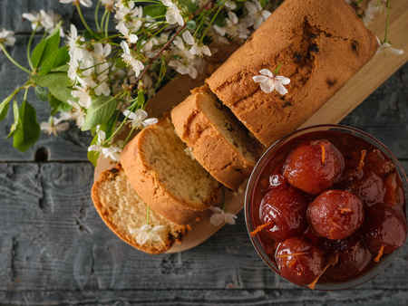 A glass bowl of whole Apple jam and a fresh cake on a wooden table. Homemade sweets according to old recipes. Flat lay. Banco de Imagens