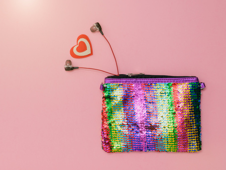 Heart and headphones sticking out of a colorful bag on a pink background. Fashion womens accessory. Flat lay. The view from the top.