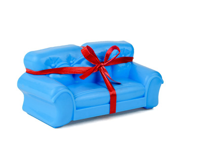 Blue sofa tied with ribbon isolated on white background. A sample of beautiful furniture for the house. Banco de Imagens