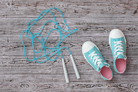 Turquoise sneakers and a high-speed jump rope on the wooden floor. Sports style. Flat lay. Banco de Imagens
