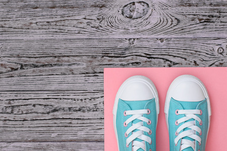 Turquoise sneakers on a pink rug on a wooden floor. Sports style. Flat lay.
