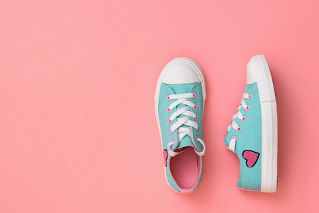 Turquoise with pink sneakers on a coral background. Color trend 2019. Sports style. Flat lay. The view from the top. Banco de Imagens
