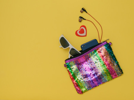 Colorful womens bag with glasses and headphones on a yellow background. Fashion womens accessory. Flat lay. The view from the top.