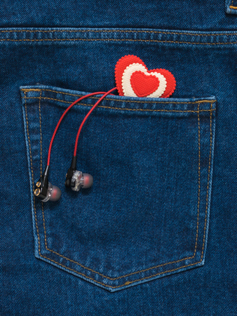 Red and white heart and red headphones in jeans pocket. Romantic style in fashionable clothes.