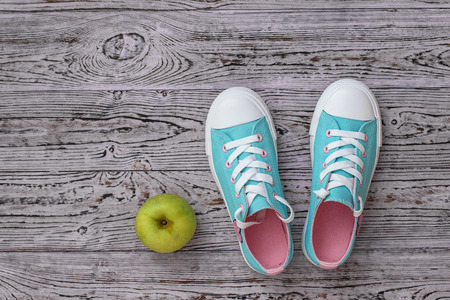 Turquoise with pink sneakers and an Apple on the wooden floor. Sports style. Flat lay. The view from the top. Banco de Imagens