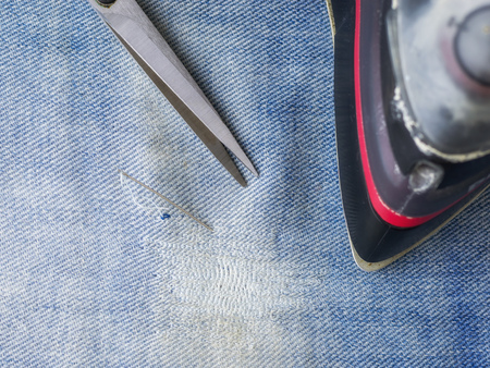 Needle and thread, scissors and iron on the background of the protection of the denim. Repair of jeans at home. The view from the top.